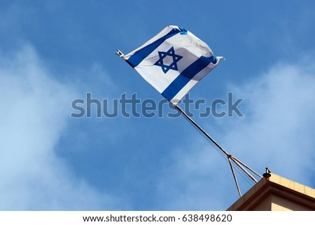 Israeli flag on a rooftop against blue sky background