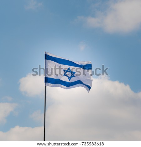 Israeli flag waving in the wind against the blue sky and white clouds on sunny day.Photo to illustrate News from Israel. Independence day Israel - Yom Ha'atzmaut .