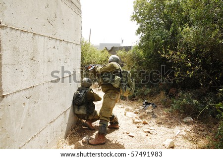 Israeli infantry soldiers looking around the corner in an urban drill in the army. This is part of regular training that every soldier does. - stock photo
