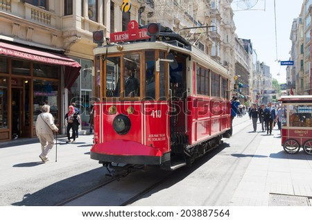 ISTANBUL - APRIL 29, 2014: Traditional red tram trundled along Istiklal Caddesi for 1.64 km (1 mile) connecting Taksim Square with Galatasaray and Tunel Square - stock photo