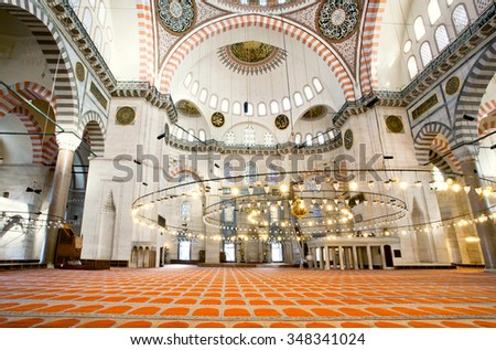 ISTANBUL - AUG 5: Interior of 16th century Suleymaniye Mosque with architectural wonders and bright lights on August 5, 2015. Ottoman imperial mosque built in 1558, religious and cultural landmark. - stock photo