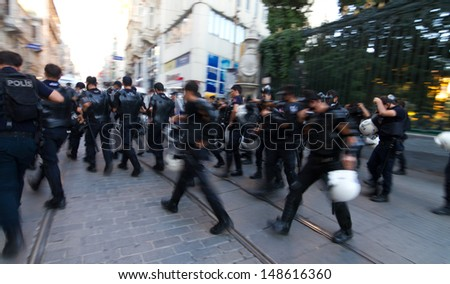 ISTANBUL - AUGUST 03: Police forces start to intervene people in Istiklal Street on August 03, 2013 in Istanbul, Turkey. Police intervene unorganized small groups of anti-government protestors.