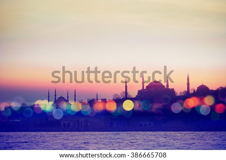 Istanbul cityscape - mosque and minarets in the evening.  Oriental blur background with  silhouette and bokeh effect. Landmarks of arabic culture in Turkey with night lights.