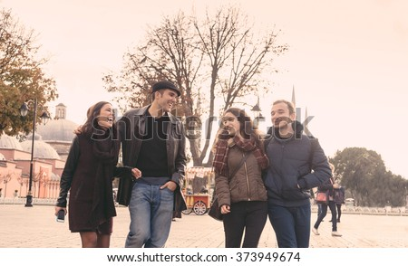 Istanbul, group of friends walking in Sultanahmet square. They are two men and two women in their mid twenties, talking and laughing while looking each other. Friendship and lifestyle concepts - stock photo