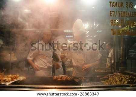ISTANBUL - JULY 25 : Cooks prepare food in busy pedestrian area of Taksim in Istanbul, Turkey on July 25, 2007. Istanbul generates 21.2% of Turkey's gross national product. - stock photo