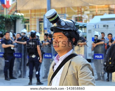 ISTANBUL - JUN 17: Five labor unions call 1-day nationwide strike over crackdown on June 17, 2013 in Istanbul, Turkey. A journalist wearing gas-mask to protect from pepper gas at Istiklal Street - stock photo