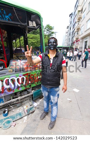 ISTANBUL - JUNE 08: Man with mask in front of damaged bus during protests on June 08, 2013 in Istanbul, Turkey. Guy Fawkes masks widely used and became a symbol of protests in Turkey.