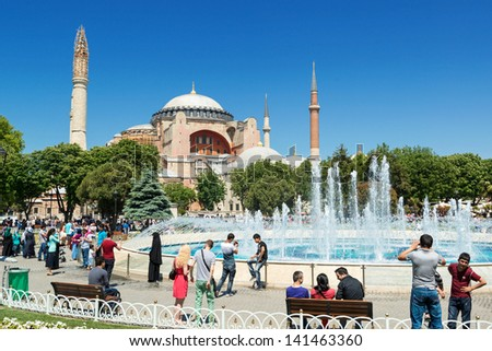 ISTANBUL - MAY 26, 2013: Tourists walk next to Hagia Sophia on may 26, 2013 in Istanbul, Turkey. Hagia Sophia is the greatest monument of Byzantine Culture and tourist attraction. - stock photo