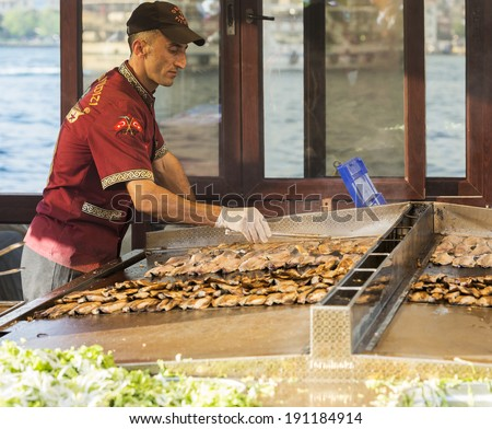ISTANBUL - MAY 02: Turkish man sells deep fried fish to tourists at Eminonu on May 02, 2014 in Istanbul. Eating on the street is a part of local life in here. entertainment and travel of Istanbul.