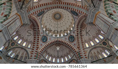 Istanbul, Turkey - April 25, 2017: Ceiling of Fatih Mosque, a public Ottoman mosque in Fatih district, Istanbul, with a huge decorated domes and colored stained glass windows