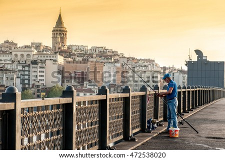 ISTANBUL, TURKEY - April 19, 2016: Fisherman on Galata Bridge with Galata tower on background on April 19, 2016 in Istanbul, Turkey. Galata Bridge is one of the famous entertainment place in Istanbul.
