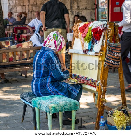 Istanbul, Turkey - Aug 26, 2013: woman weaver makes traditional Turkish carpet on the streets of Istanbul. Carpets is one of traditional souvenirs in Turkey - stock photo