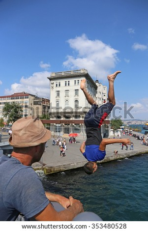 ISTANBUL, TURKEY - AUGUST 09, 2015: A kid flipping into the Golden Horn from the Galata bridge.  - stock photo