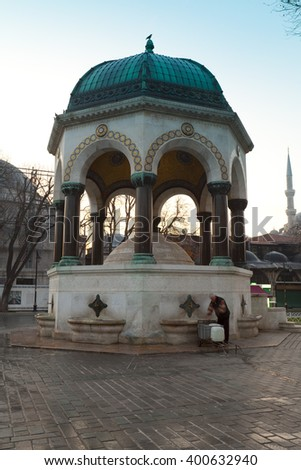 ISTANBUL,TURKEY - DEC 29 : Turkish guy collecting water from German Fountain at Sultanahmet Square,famous district of Istanbul containing many landmarks in Istanbul ,Turkey on Dec 29,2015. - stock photo
