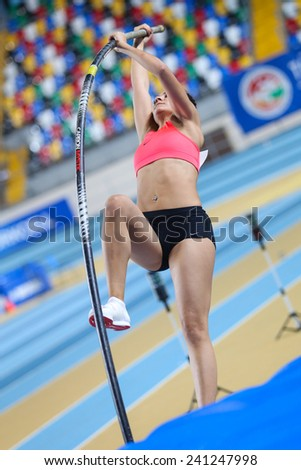 ISTANBUL, TURKEY - DECEMBER 27, 2014: Athlete Elmas Seda Firtina pole vaulting during Athletics record attempt races in Asli Cakir Alptekin Athletics hall, Istanbul. - stock photo