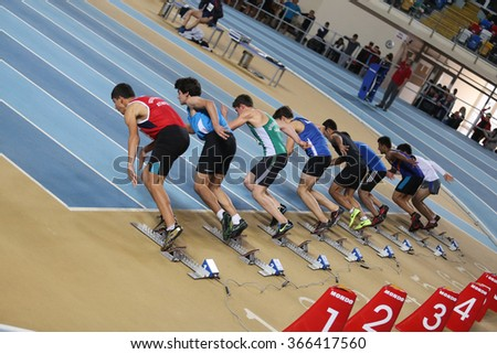ISTANBUL, TURKEY - DECEMBER 26, 2015: Athletes run 60 metres race during Turkish Athletic Federation Indoor Athletics Record Attempt Races - stock photo