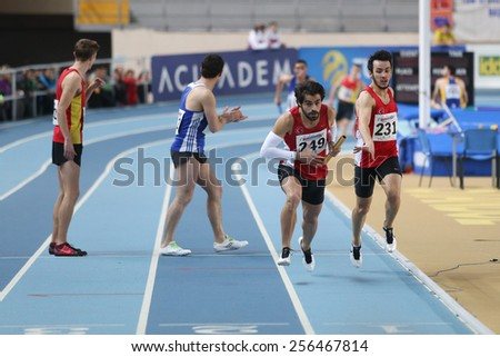 ISTANBUL, TURKEY - FEBRUARY 21, 2015: Athletes running 4x400 relay race during Balkan Athletics Indoor Championships in Asli Cakir Alptekin Athletics hall.