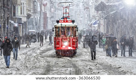 ISTANBUL,TURKEY- February 18: Unidentified pedestrians walk down Istiklal Street on a snowy day on February 18, 2015 in Istanbul, Turkey.Istiklal Street is one of the popular destinations in Istanbul. - stock photo