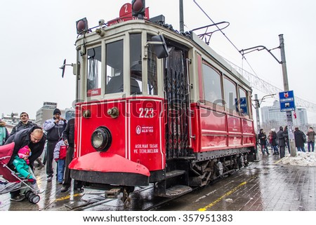 ISTANBUL, TURKEY - JANUARY 3, 2016: Retro tram moves along a busy Istiklal street in Istanbul. Red train to Istiklal Street after rainy and snow
