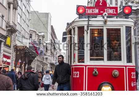 ISTANBUL, TURKEY - JANUARY 1, 2016: Snowy day in Taksim, Istanbul. Taksim Istiklal Street is a popular destination in Istanbul. Nostalgic tram, sellers and peoples.