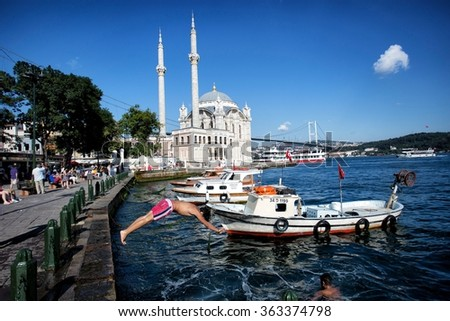 Istanbul, Turkey - July 05, 2014: Istanbul in the background, the Bosphorus Bridge, The Ortakoy Mosque in Turkey who jumped into the sea in front of the guys