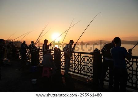 Istanbul, Turkey - July 5, 2015: People fishing at dawn on Galata Bridge in Istanbul - stock photo
