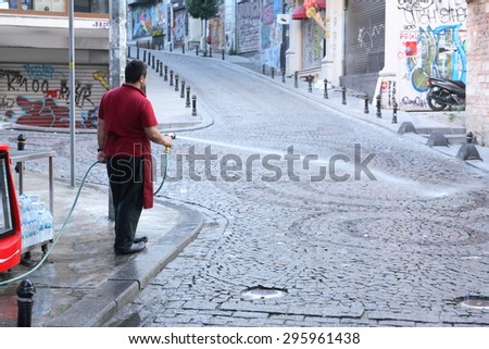 Istanbul, Turkey - July 5, 2015: Shop owner washing street early in the morning
