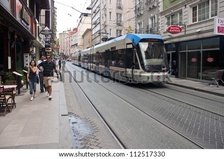 ISTANBUL, TURKEY - JULY 13: Unidentified people and a tram at a street. July 13, 2011 in Istanbul, Turkey. Istanbul is the only metropolis in the world situated on two continents.