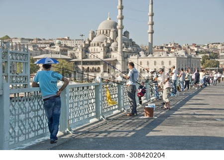 ISTANBUL, TURKEY - JULY 30: Unidentified Turkish fishermen fish rod on Galata Bridge on July 30, 2013 in Istanbul, Turkey. For most of them it's only hobby, not source of food or income. - stock photo