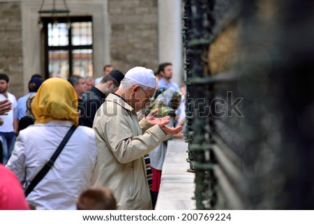 ISTANBUL, TURKEY - JUNE 23: Eyup Sultan Tomb. praying in front of people  on June 23, 2014 in Istanbul, Turkey. Close friend of the Prophet's tomb in Istanbul Eyup Sultan is the most visited place. - stock photo