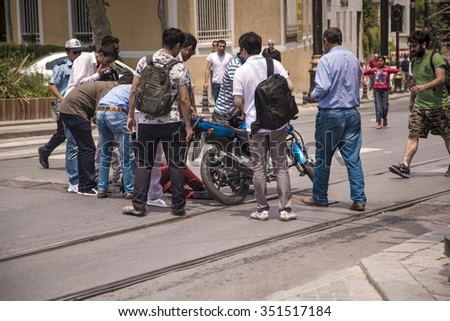 Istanbul, Turkey - June 14, 2015: Motorcycle accident with a lot of Turkish people helping the driver to get stood in city center