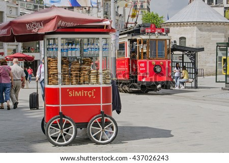 ISTANBUL, TURKEY - JUNE 5, 2016:  The nostalgic tram beside a cart selling traditional Turkish simit at the Taksim end of the famous Istiklal Caddesi.  Tourists and locals enjoy the sunshine.
