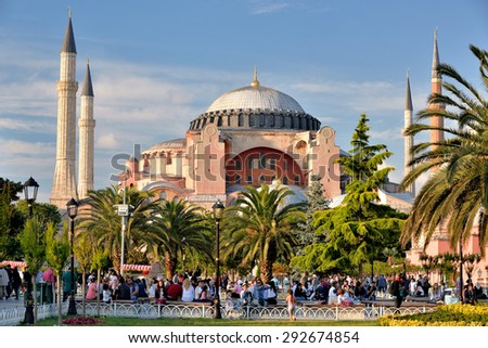 ISTANBUL, TURKEY - JUNE 23, 2015: Tourists rest and socialize in the park in front of Hagia Sophia, located in Istanbul, in Turkey.  - stock photo