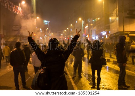 ISTANBUL, TURKEY - MARCH 11, 2014: A woman shows the victory sign in Kadikoy during protest after Berkin Elvan, who was 15 years old, died. He was hit in the head with a tear gas canister by Police. - stock photo