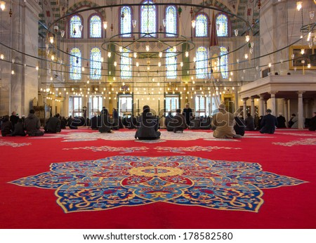 Istanbul, Turkey - 23 March, 2013: Muslim men gathered in Fatih Mosque for the prayer. This mosque has been built by the Ottomans in 1470 just beside the tomb of Fatih Sultan Mehmed. - stock photo