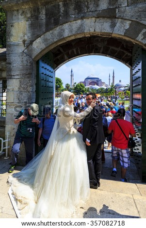 ISTANBUL, TURKEY - MAY 25: A very happy couple leave the Blue Mosque after their wedding. In the background Hagia Sophia on May 25, 2014 Istanbul, Turkey.  - stock photo