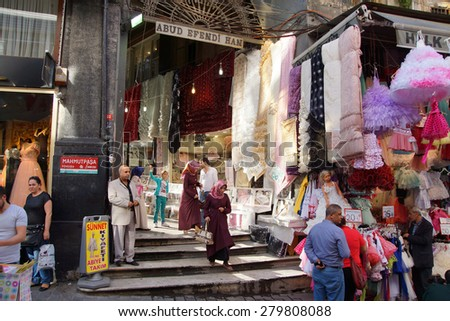 ISTANBUL, TURKEY - MAY 17, 2014 -Locals shop for children's clothes in the narrow streets near the Egyptian Bazaar,  in Istanbul, Turkey - stock photo