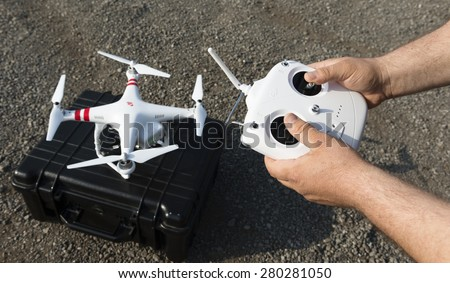 ISTANBUL, TURKEY - MAY 19 ,2015: Operator holding remote control .A stationary Phantom quadcopter and remote controller, manufactured by the company DJI Innovations.  - stock photo
