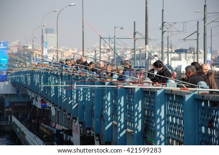 ISTANBUL, TURKEY - NOV 22, 2011 - Fishermen on Galata Bridge  in Istanbul. The bridge is well known for rod fishing in here