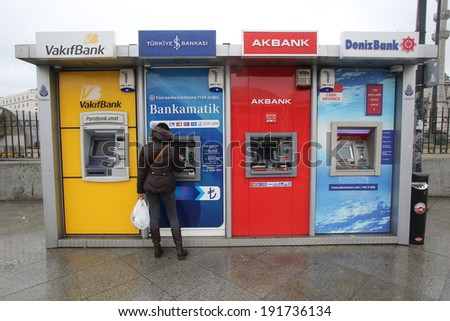 ISTANBUL, TURKEY - Saturday, March 8, 2014: A woman accesses money from an ATM machine in Istanbul, Turkey, on Saturday, March 8, 2014.  - stock photo