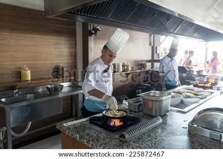 ISTANBUL TURKEY SEPT 28, 2014: Chef in restaurant kitchen doing flambe on food