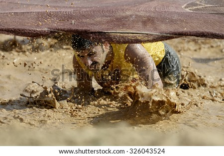 ISTANBUL, TURKEY, 13 SEPTEMBER 2014, A Participant trying pass puddle stage in Mud Race in Istanbul.