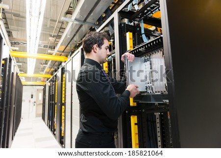 IT administrator installing a new rack mount server - stock photo