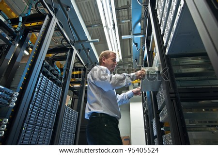 IT administrator installing a new rack mount server. Large scale storage server is also seen. - stock photo