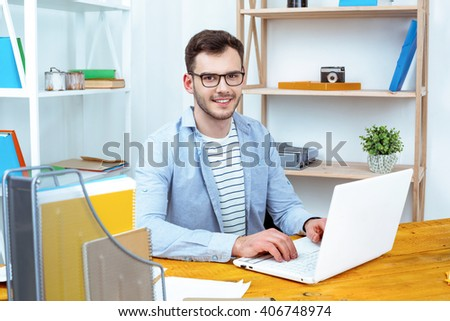 IT company. Young programmer working with laptop. Nice office interier. Professional coder looking at camera and smiling - stock photo