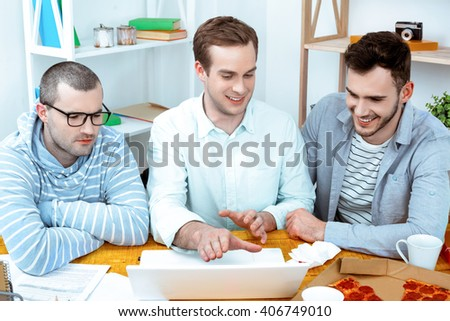 IT company. Young programmers working with laptop with pizza. Nice office interier. Professional coders looking at laptop and smiling - stock photo