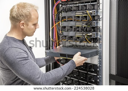 IT consultant build network racks in datacenter - stock photo