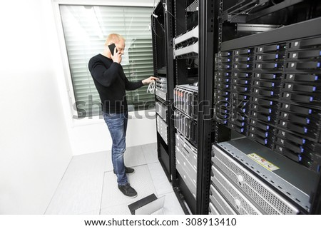 IT consultant solving problem with support in datacenter - stock photo