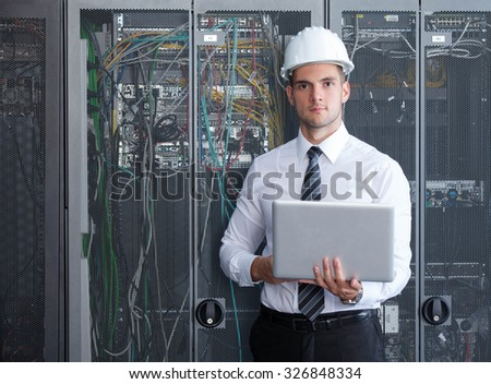 it engeneer businessman with thin modern aluminium laptop in network server room - stock photo