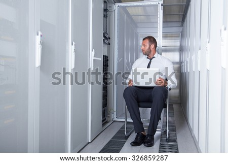 it engeneer businessman with thin modern aluminium laptop in network server room